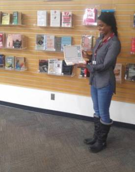 A VPL staff member stands in front of books on display reading a story.